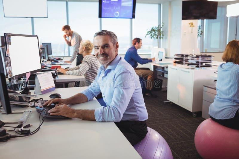 Retrato del hombre de negocios sonriente que trabaja en el escritorio mientras que se sienta en bola del ejercicio fotos de archivo libres de regalías