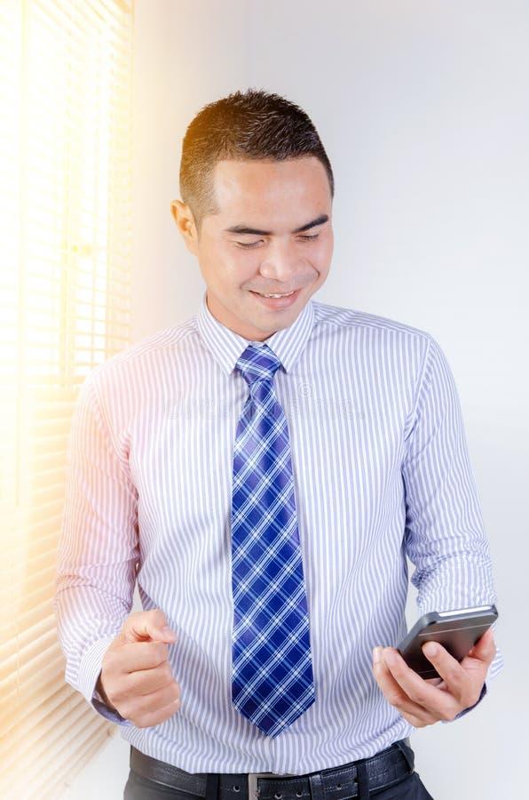 Retrato del hombre de negocios tailandés asiático de la sonrisa que mira a smar móvil foto de archivo