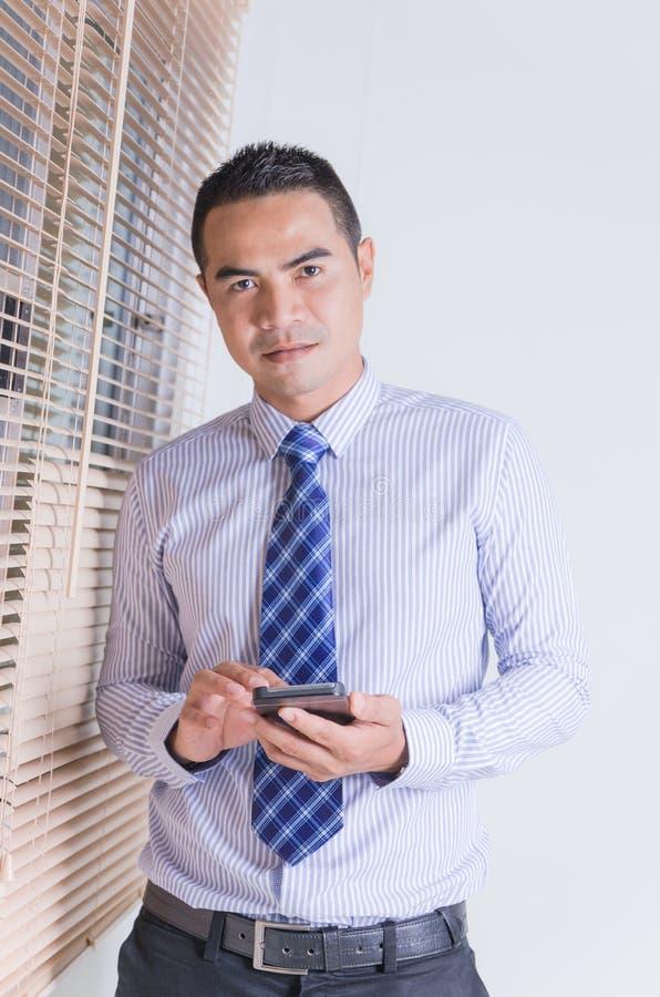Retrato del hombre de negocios tailandés asiático de la sonrisa que usa pho elegante móvil imagen de archivo libre de regalías