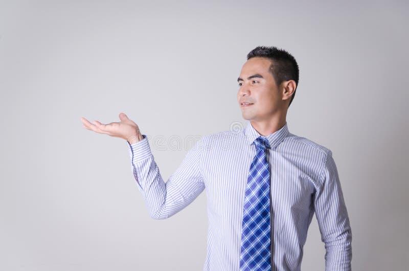 Retrato del hombre de negocios tailandés asiático que muestra la mano en blanco como el control foto de archivo