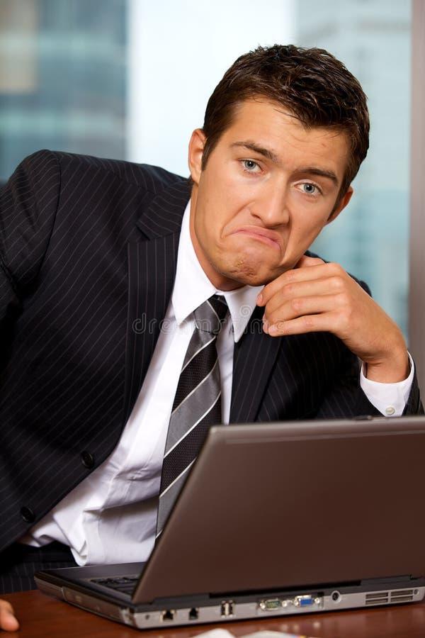 Retrato del hombre de negocios triste que se sienta en oficina imagen de archivo