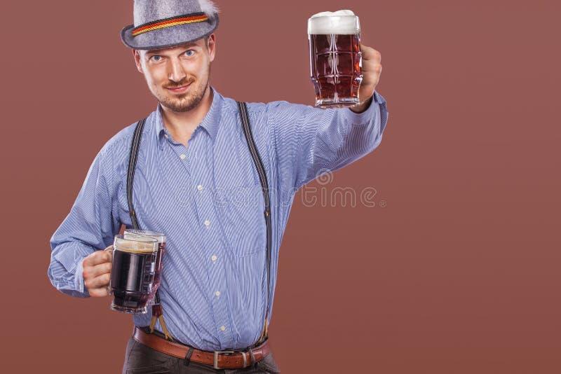 Retrato del hombre de Oktoberfest en el sombrero, el llevar ropa bávara tradicional, tazas de cerveza grandes de servicio fotografía de archivo