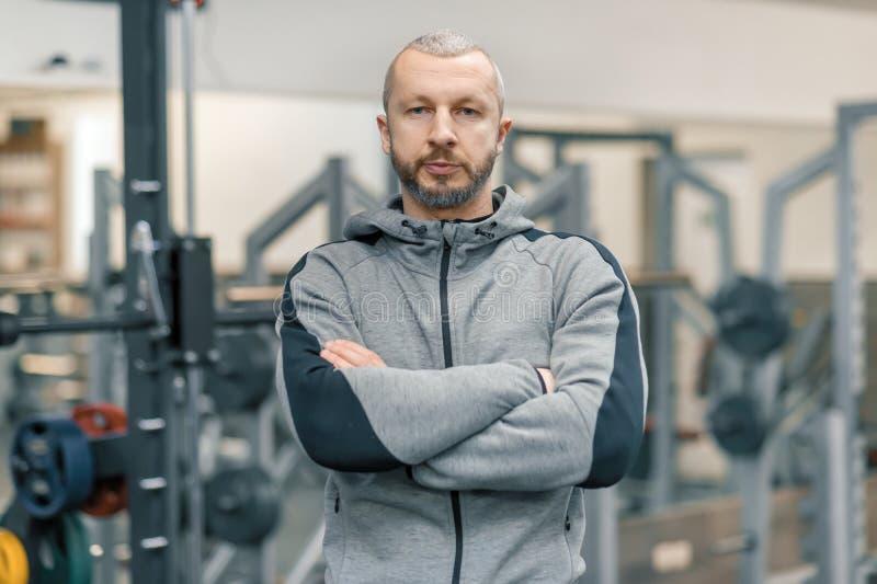 Retrato del hombre deportivo hermoso con las manos dobladas en el gimnasio, instructor cruzado de la aptitud que mira la c?mara fotografía de archivo