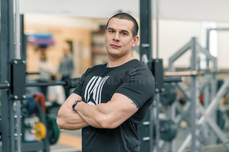 Retrato del hombre deportivo muscular con las manos dobladas en el gimnasio, instructor hermoso que mira la cámara foto de archivo libre de regalías