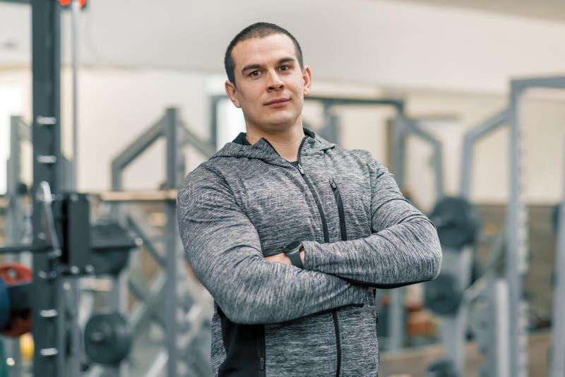 Retrato del hombre deportivo muscular con las manos dobladas en el gimnasio, instructor hermoso que mira la cámara foto de archivo