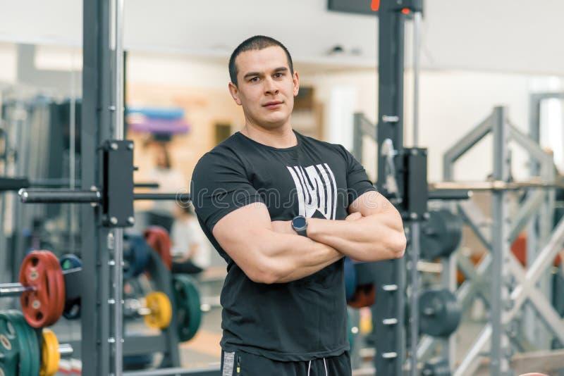Retrato del hombre deportivo muscular en el gimnasio, instructor de gimnasio profesional hermoso que mira la cámara fotos de archivo