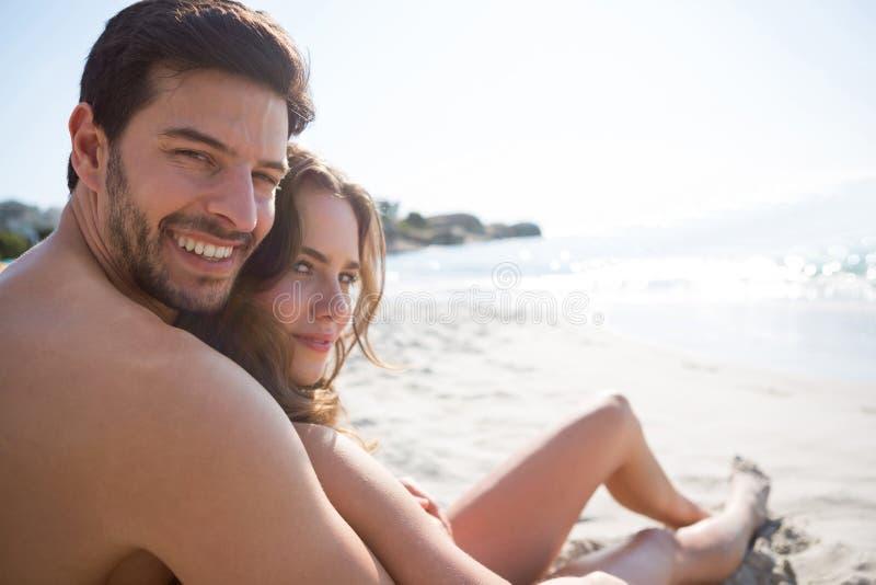 Retrato del hombre descamisado joven con su novia que se sienta en la playa imagen de archivo