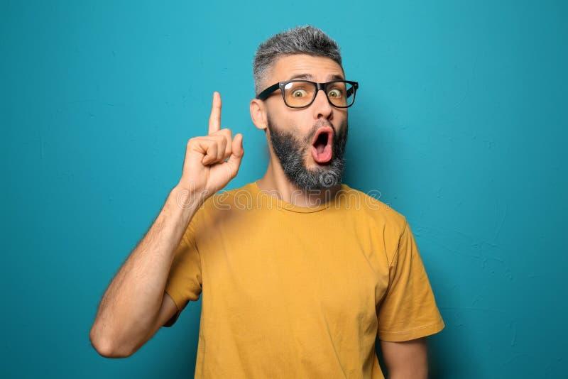 Retrato del hombre emocional con el dedo índice aumentado en fondo del color imagenes de archivo