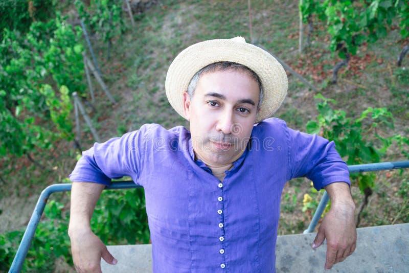 Retrato del hombre en el sombrero de paja que se sienta en banco en la colina imágenes de archivo libres de regalías