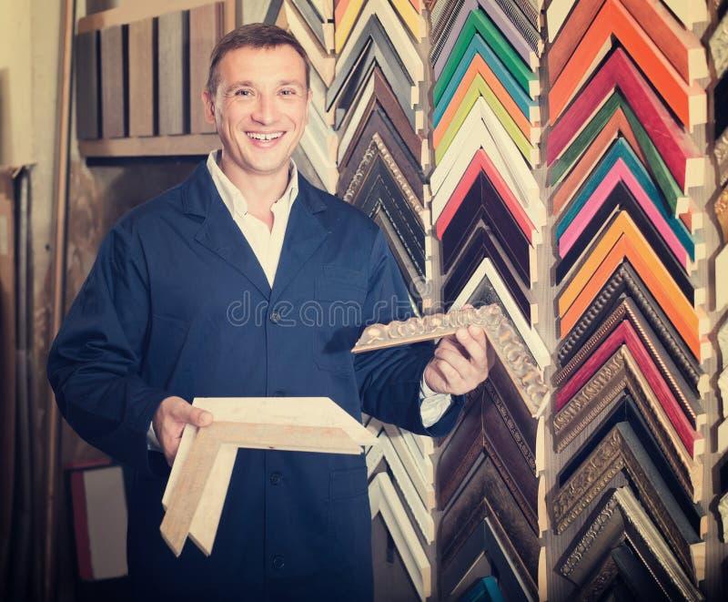 Retrato del hombre en el uniforme que elige moldear que enmarca en estudio fotografía de archivo libre de regalías