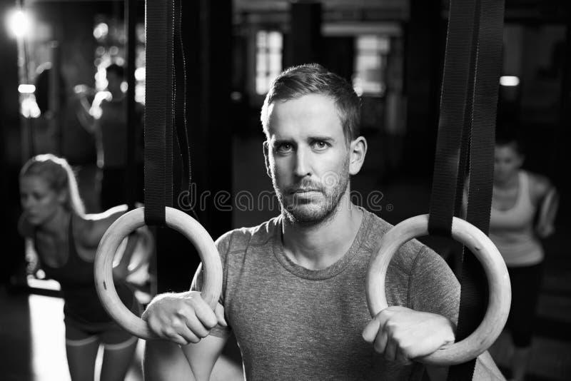 Retrato del hombre en gimnasio que ejercita con los anillos gimnásticos fotografía de archivo libre de regalías