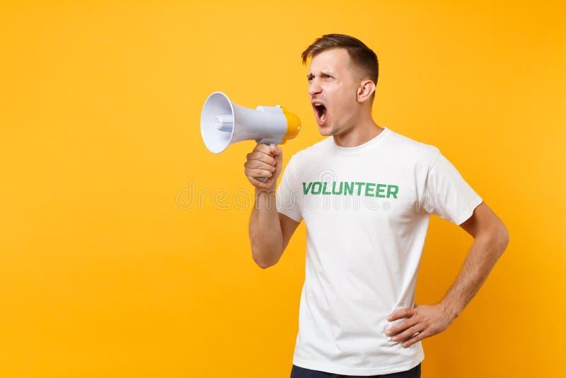 Retrato del hombre en grito voluntario escrito camiseta blanca del título del verde de la inscripción en el megáfono de la megafo imagenes de archivo