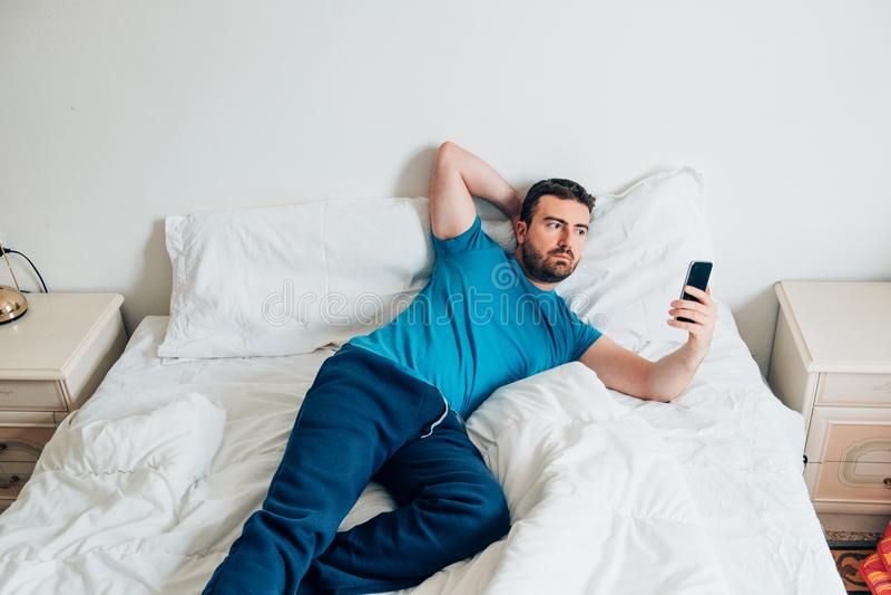 Retrato del hombre en la cama blanca usando smartphone fotografía de archivo libre de regalías