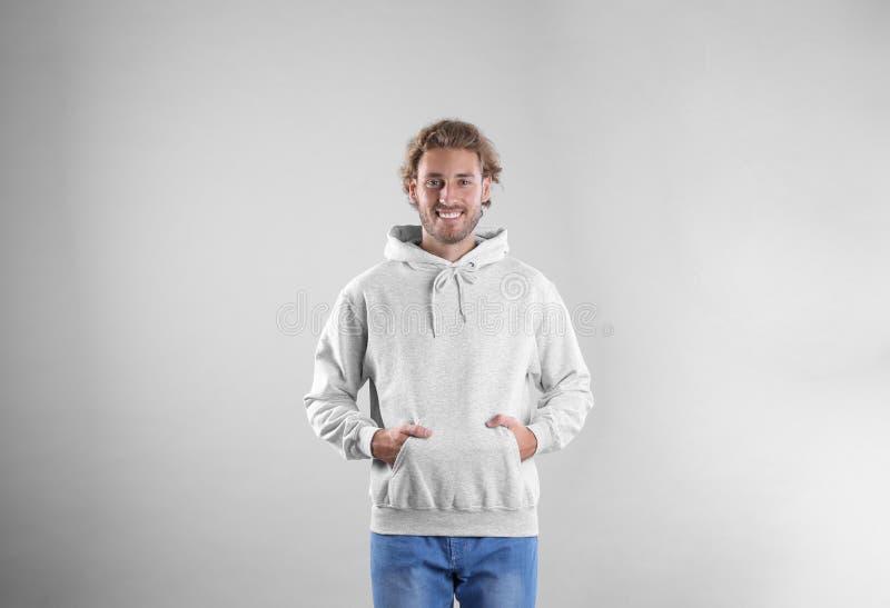 Retrato del hombre en suéter de la sudadera con capucha en fondo ligero imagen de archivo