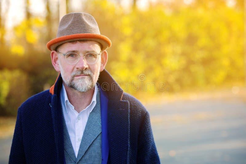 Retrato del hombre en su 50s en aire libre azul del traje y de la capa fotografía de archivo