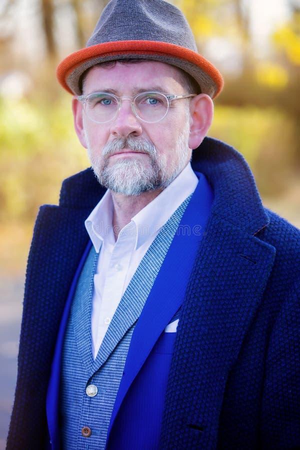 Retrato del hombre en su 50s en aire libre azul del traje y de la capa fotos de archivo