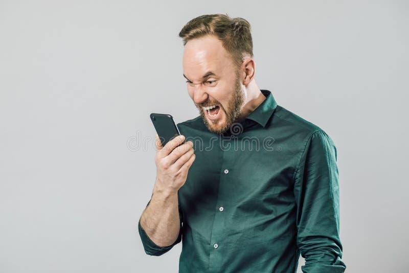 Retrato del hombre enojado que grita en el altavoz de su smartphone fotos de archivo libres de regalías