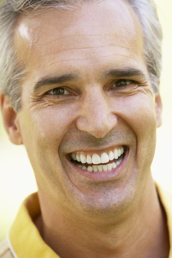 Retrato del hombre envejecido medio que sonríe en la cámara imagen de archivo