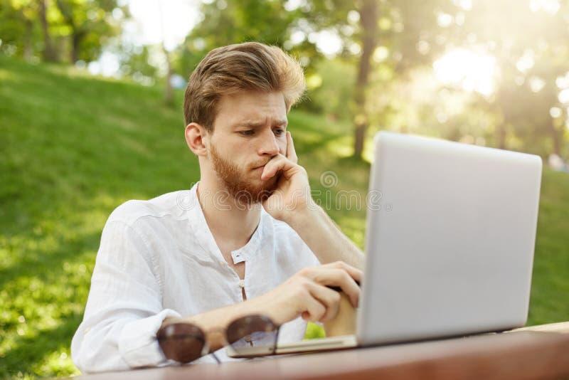 Retrato del hombre europeo atractivo pensativo con el corte de pelo elegante que mira en el monitor del ordenador portátil que es fotografía de archivo