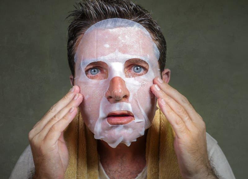 Retrato del hombre extra?o y divertido joven en casa que intenta usando la m?scara facial del papel de la belleza que limpia apre foto de archivo libre de regalías