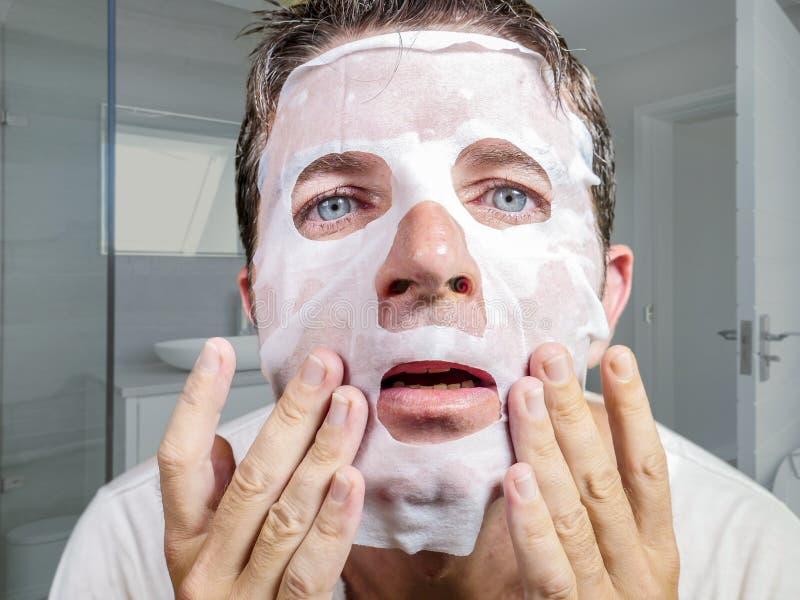 Retrato del hombre extra?o y divertido joven en casa que intenta usando la m?scara facial del papel de la belleza que limpia apre imagen de archivo