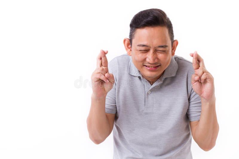 Retrato del hombre feliz, contento que cruza su finger fotos de archivo