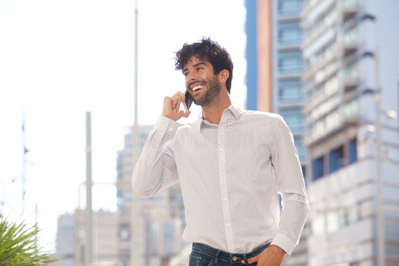 Retrato del hombre feliz que ríe y que habla en el teléfono elegante afuera imagenes de archivo