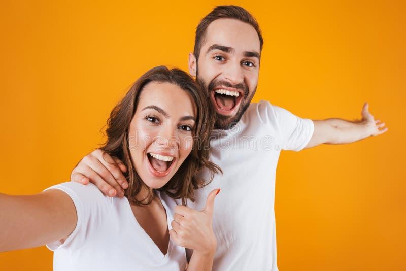 Retrato del hombre feliz y de la mujer de dos personas que sonríen mientras que toma la foto del selfie, aislado sobre fondo amar fotografía de archivo libre de regalías