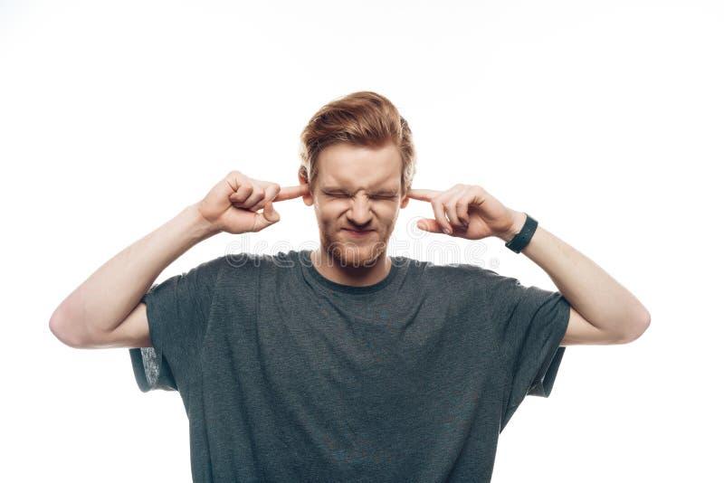 Retrato del hombre frustrado que sostiene los fingeres en oídos fotografía de archivo