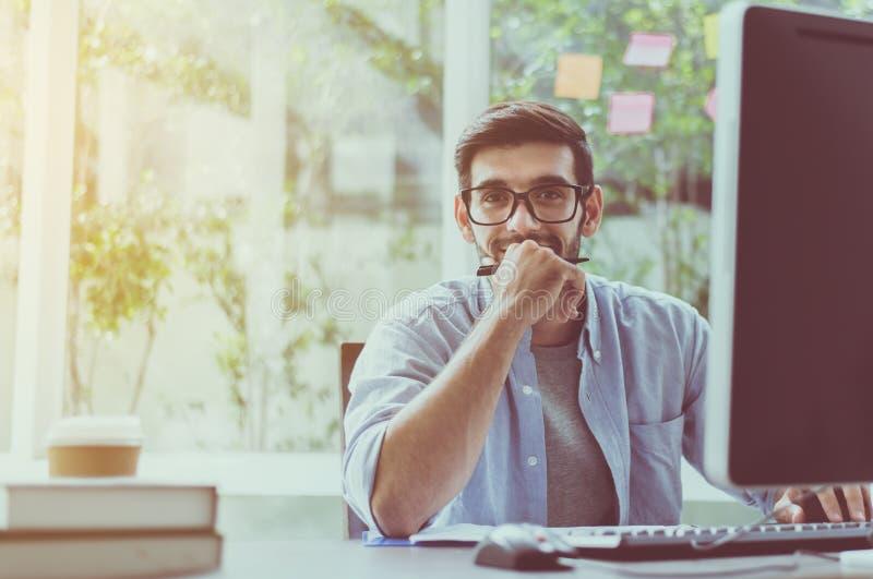 Retrato del hombre hermoso con la barba mientras que trabaja en línea en casa, feliz y la sonrisa imágenes de archivo libres de regalías
