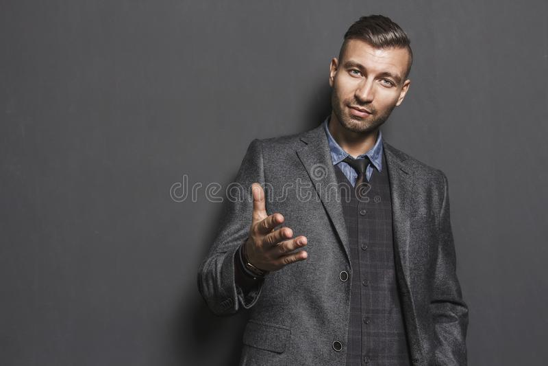 Retrato del hombre hermoso elegante que estira hacia fuera su mano mirada confiada del hombre acertado de moda en traje gris imágenes de archivo libres de regalías