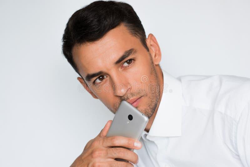 Retrato del hombre hermoso enviar el texto en el teléfono móvil aislado contra fondo gris Idea de la tecnología y de la conexión fotografía de archivo libre de regalías