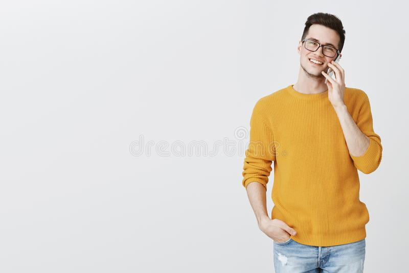 Retrato del hombre hermoso joven carismático feliz en vidrios y mano de moda amarilla de la tenencia del suéter en el bolsillo re imagen de archivo libre de regalías