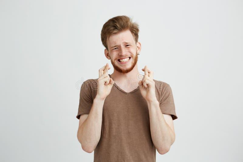 Retrato del hombre hermoso joven con esperar de rogación de la barba sobre el fondo blanco imagenes de archivo