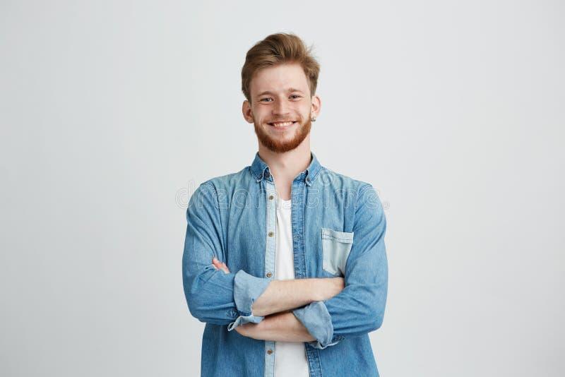 Retrato del hombre hermoso joven en camisa de la mezclilla que sonríe mirando la cámara con los brazos cruzados sobre el fondo bl foto de archivo libre de regalías