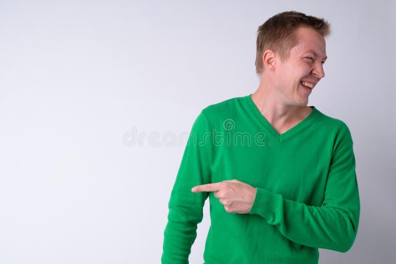 Retrato del hombre hermoso joven feliz que ríe y que señala al lado foto de archivo libre de regalías