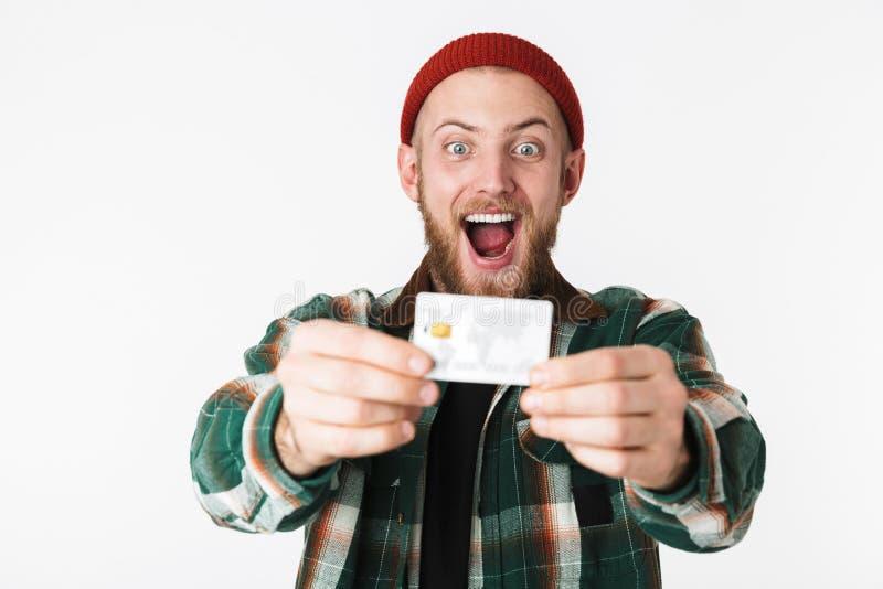 Retrato del hombre del inconformista que ríe y que sostiene la tarjeta de crédito, mientras que se coloca aislado sobre el fondo  fotografía de archivo libre de regalías
