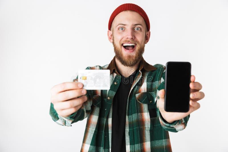 Retrato del hombre del inconformista que sostiene la tarjeta de crédito y el teléfono celular, mientras que se coloca aislado sob fotografía de archivo