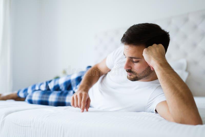 Retrato del hombre infeliz que miente en cama foto de archivo libre de regalías