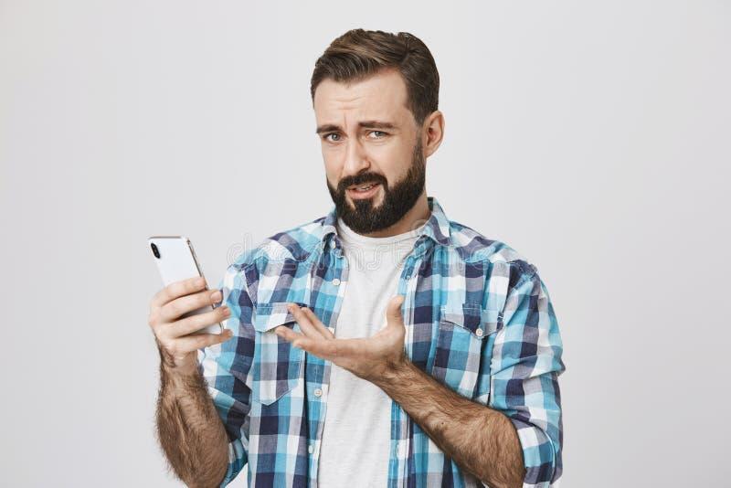 Retrato del hombre insatisfecho que sostiene smartphone y que gesticula con otra mano, expresando la aversión y la decepción imágenes de archivo libres de regalías