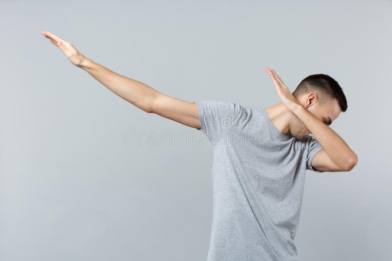 Retrato del hombre joven alegre en la ropa casual que muestra gesto de la danza del lenguado aislado en fondo gris de la pared en fotografía de archivo libre de regalías