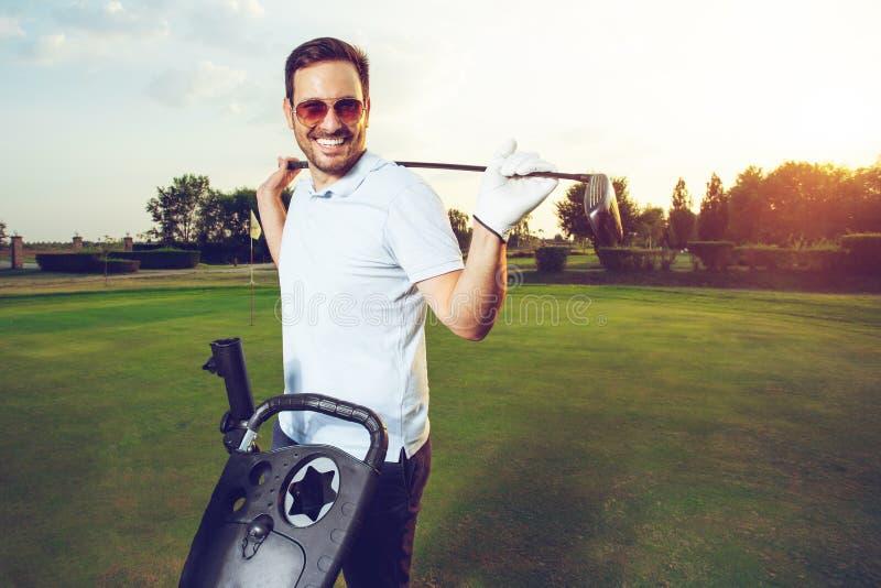 Retrato del hombre joven alegre que detiene al club de golf mientras que se coloca en campo fotos de archivo