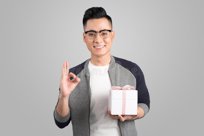 Retrato del hombre joven asiático que sostiene la caja de regalo sobre gris fotos de archivo libres de regalías