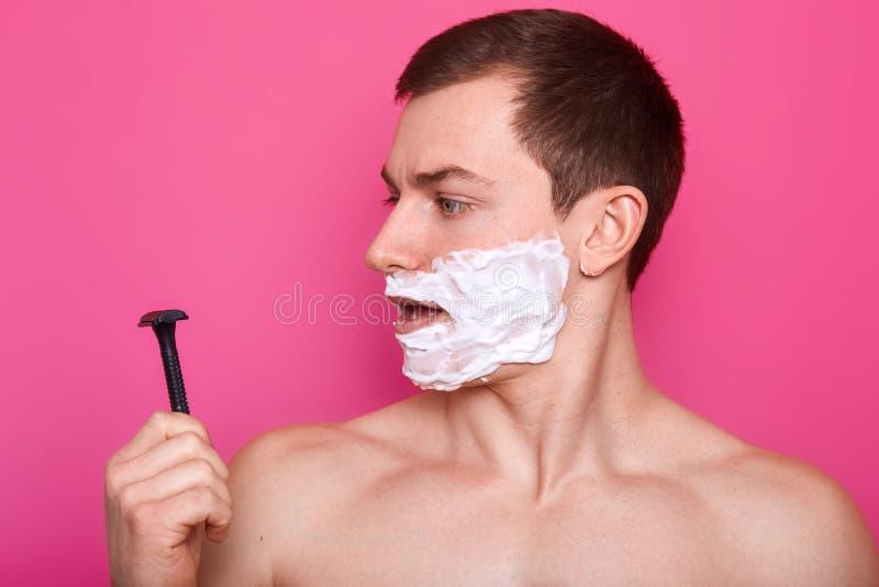 Retrato del hombre joven atractivo con espuma por todo su cara que mira la maquinilla de afeitar mientras que se coloca con la ex imagenes de archivo