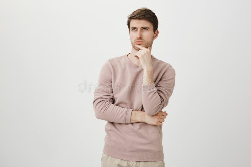 Retrato del hombre joven atractivo con la cerda que mira para arriba mientras que toca la barbilla y piensa en algo, colocándose  imagenes de archivo
