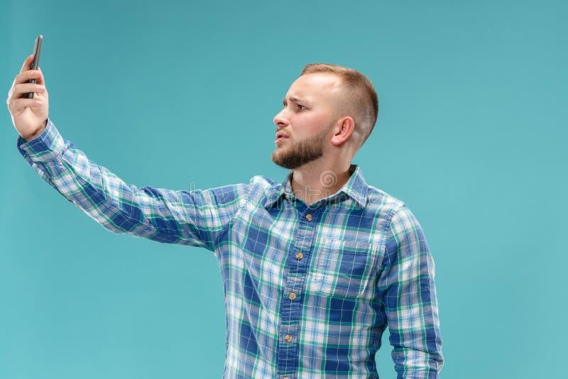 Retrato del hombre joven atractivo que toma un selfie con su smartphone Aislado en fondo azul foto de archivo libre de regalías