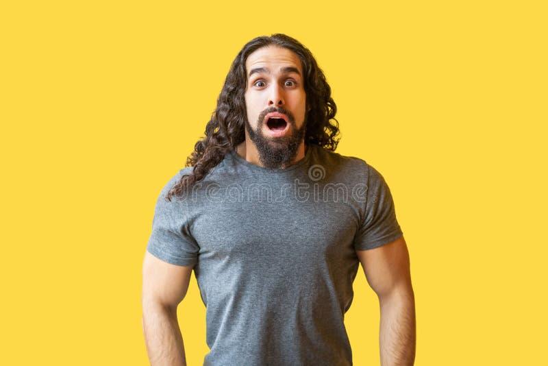 Retrato del hombre joven barbudo chocado con el pelo rizado largo en la situación gris de la camiseta y de mirar la cámara con la fotografía de archivo