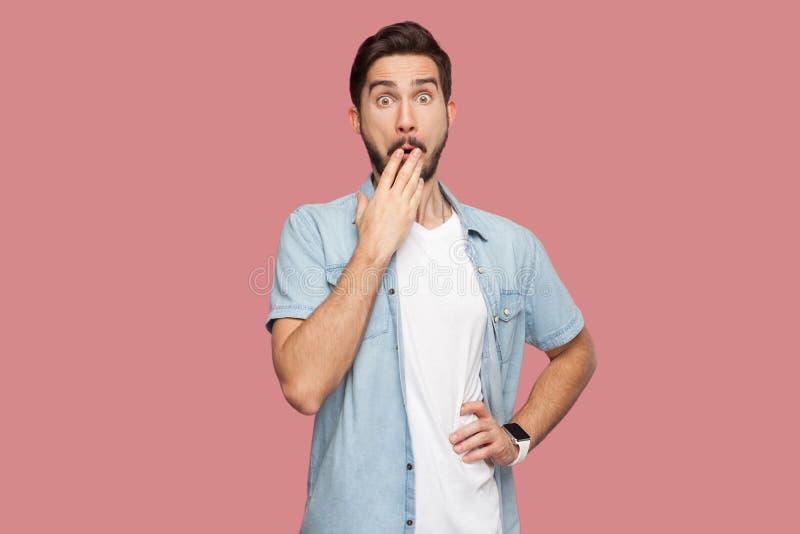 Retrato del hombre joven barbudo chocado en la situación azul de la camisa del estilo sport con los ojos grandes, cubriendo su bo fotos de archivo libres de regalías