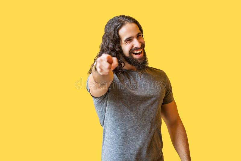 Retrato del hombre joven barbudo feliz con el pelo rizado largo en la camiseta gris que coloca, señalando y mirando la cámara con fotos de archivo