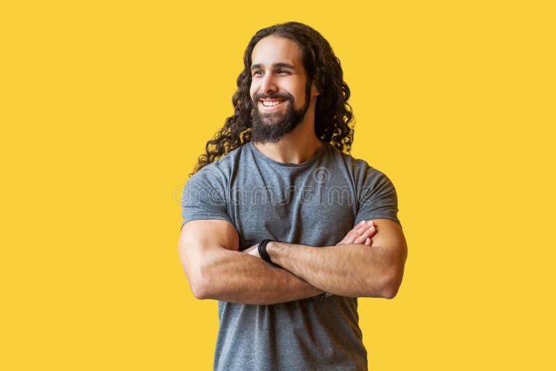 Retrato del hombre joven barbudo feliz hermoso con el pelo rizado largo en la situación gris de la camiseta con los brazos cruzad foto de archivo libre de regalías